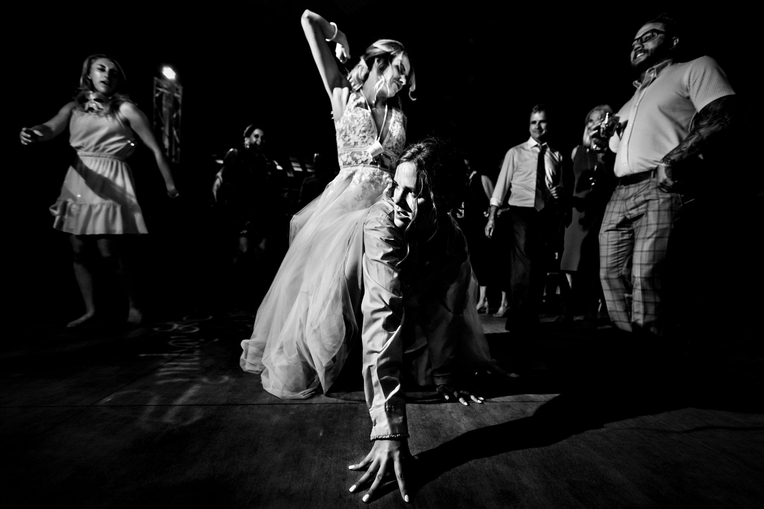Bride dances as she rides on her friend's back at the wedding reception.