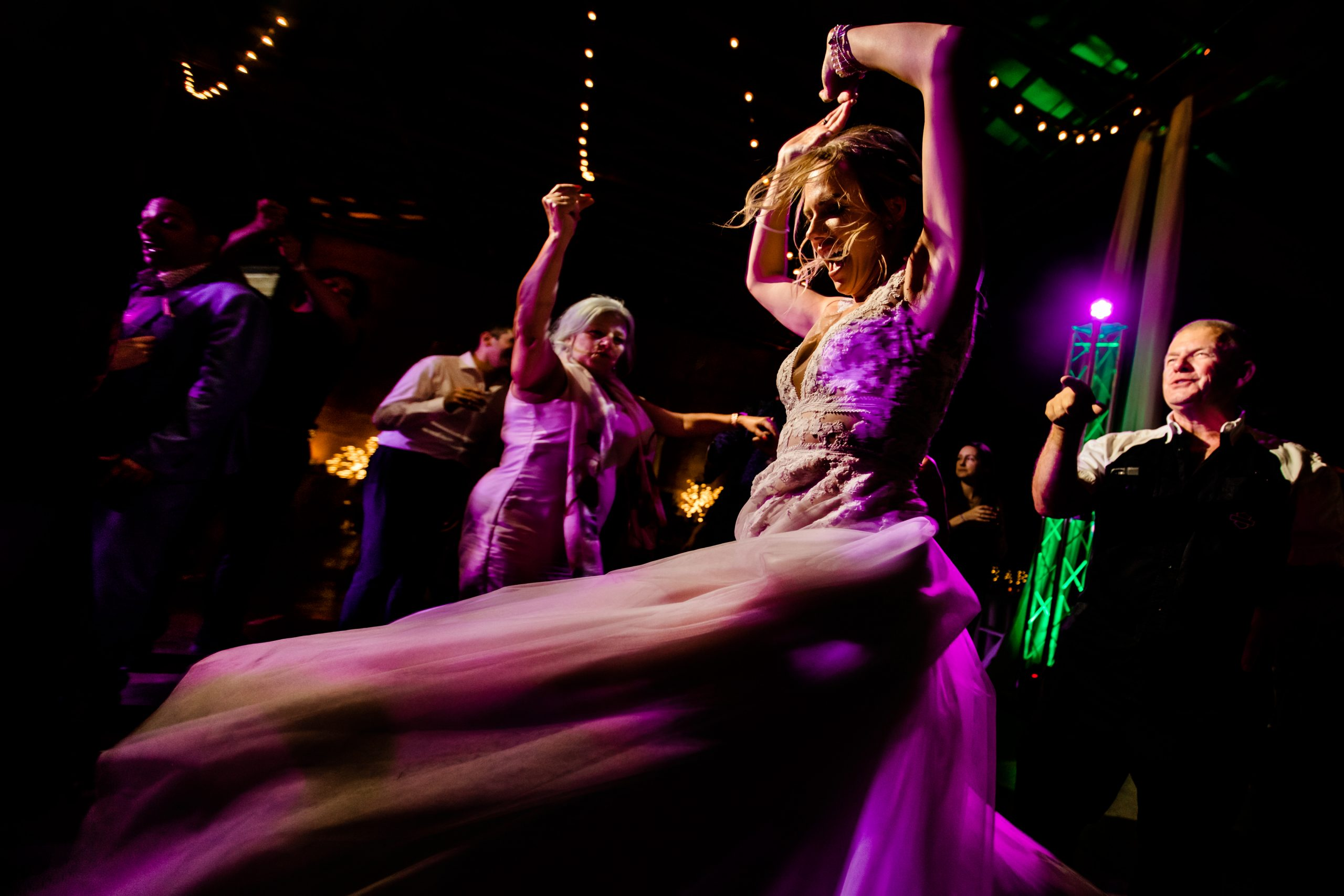 Bride's dress flows as she dances at her wedding reception.