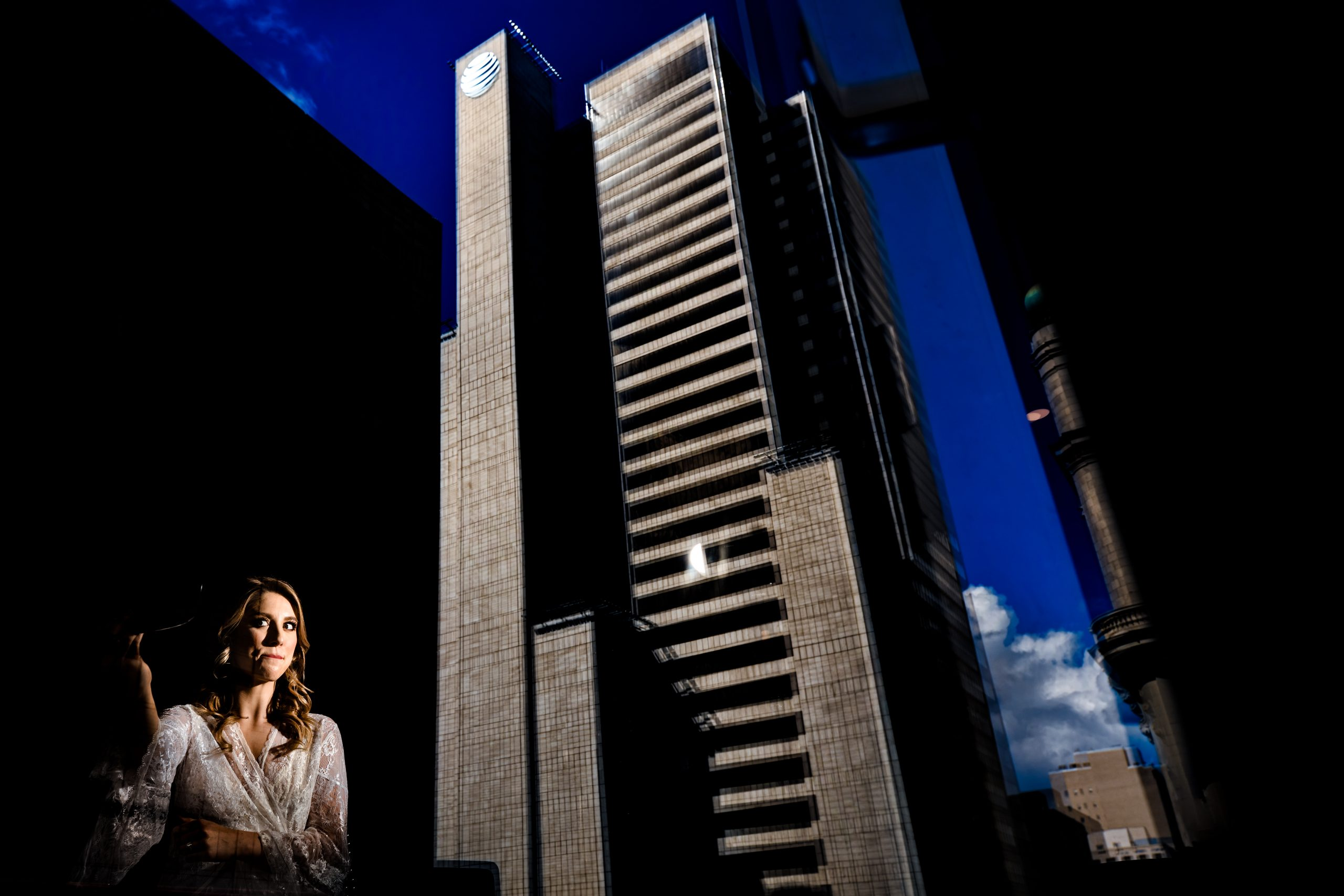 Bride prepares for her wedding with the reflection of a high-rise building.