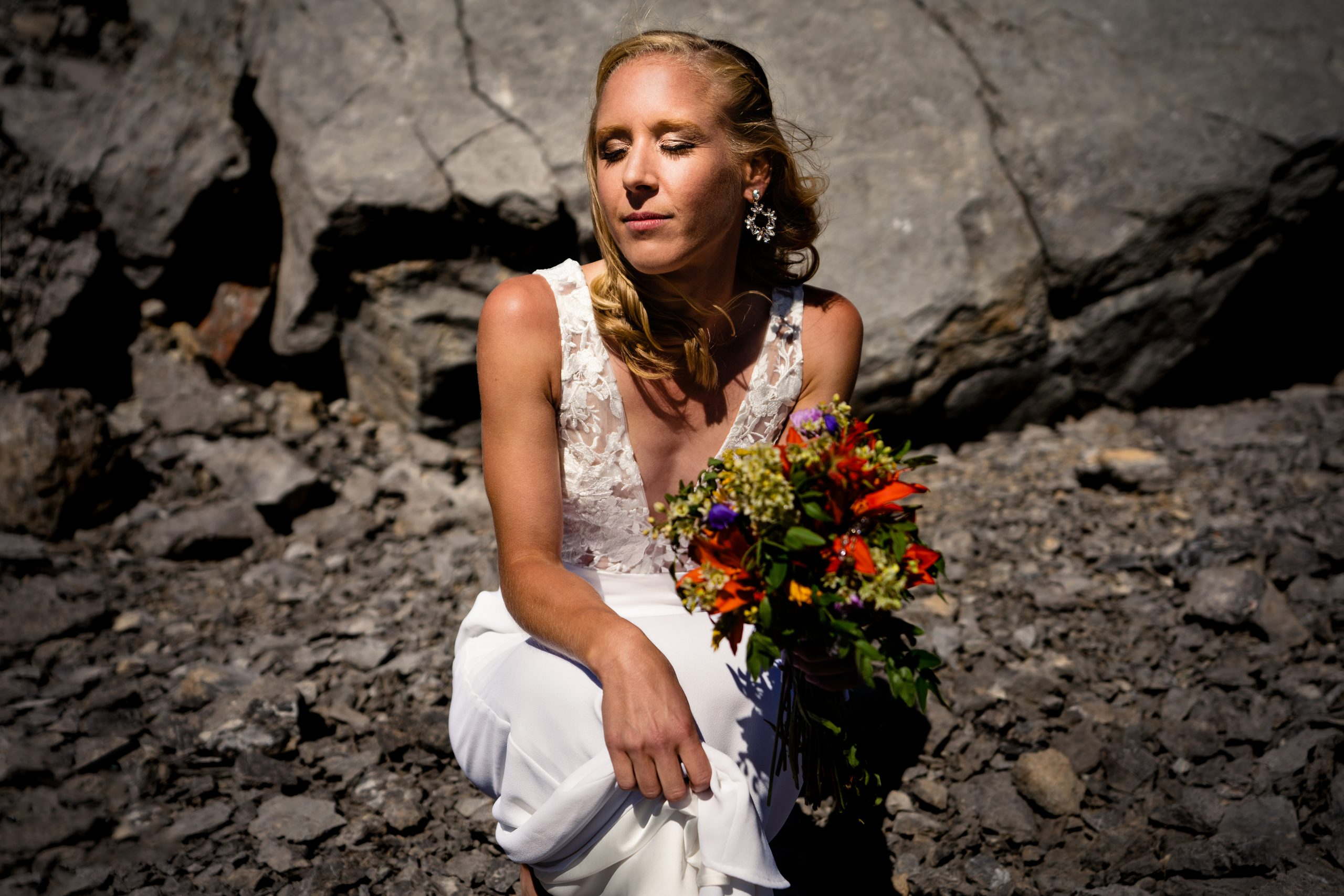 photo of a bride on a mountain posing with a flower bouquet