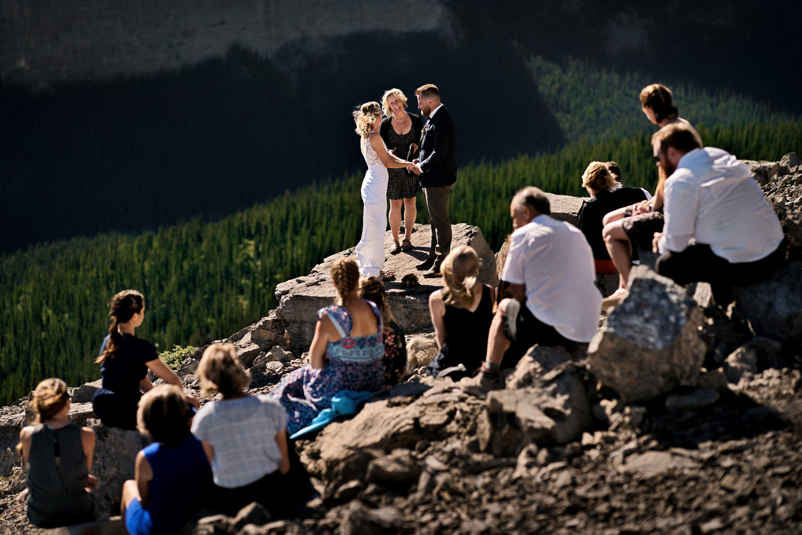 photo of a couple getting married at the top of a mountain while friends watch