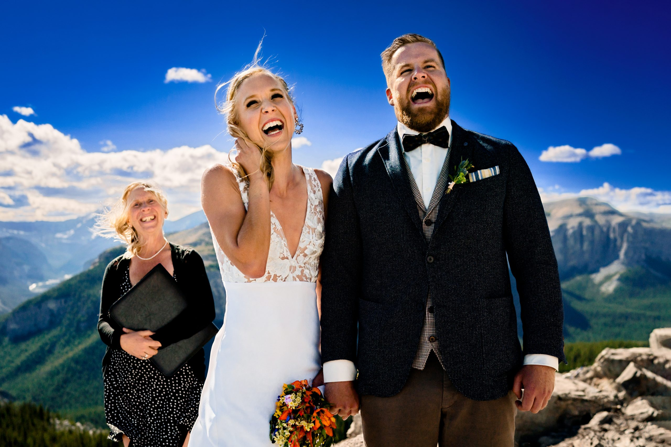 photo of a groom and a bride smiling after getting married on top of a mountain