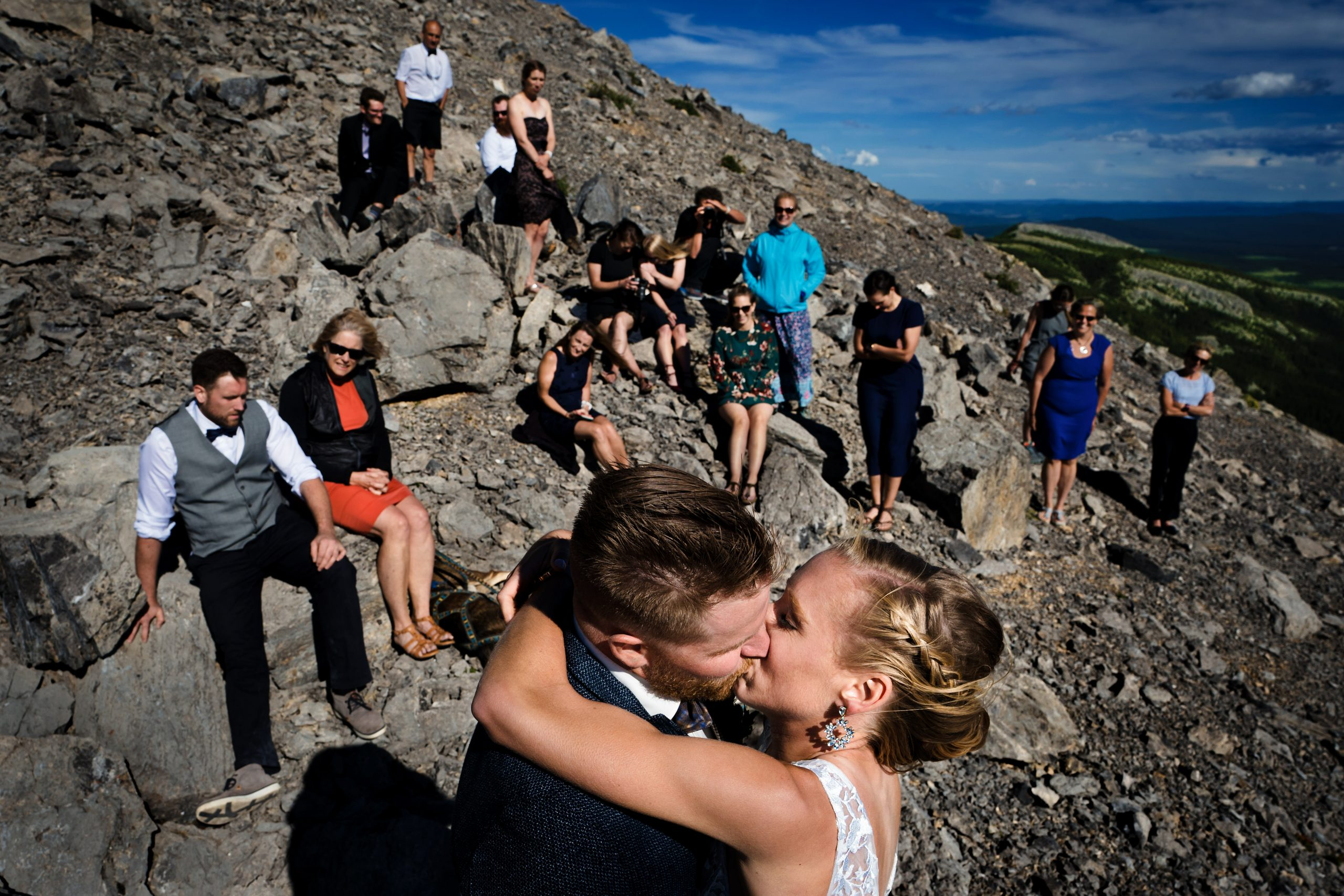 photo of bride and groom kissing with wedding guests in the background on top of a moutain