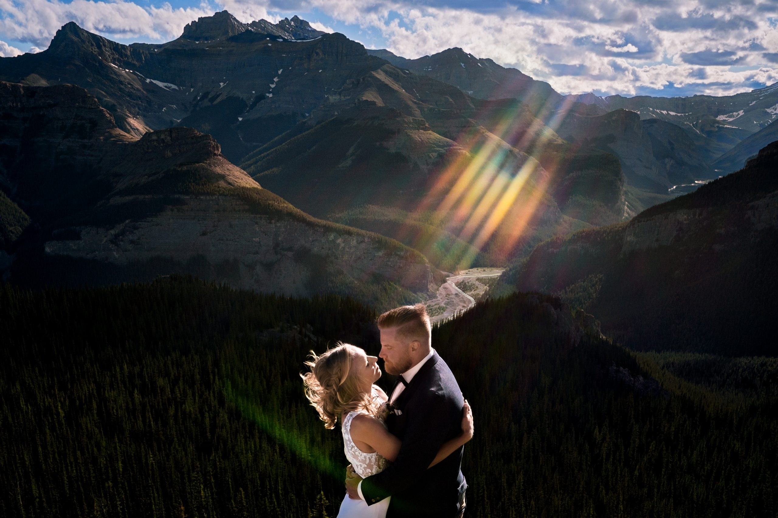photo of bride and groom hugging at the top of a mountain